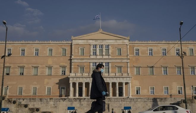 A man wearing a protective face mask and gloves to prevent the spread of the coronavirus walks in front of the Greek parliament in Athens, on Wednesday, Feb. 3, 2021. Greek authorities reimpose tougher lockdown restrictions in greater Athens after a January decline in infection rates was reversed this week. (AP Photo/Petros Giannakouris)