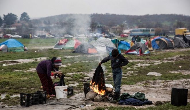 A migrant boy is trying to dry a jacket over a camp fire in a makeshift camp at the Greek - FYROM border near the Greek village of Idomeni, Greece on March 12, 2016.