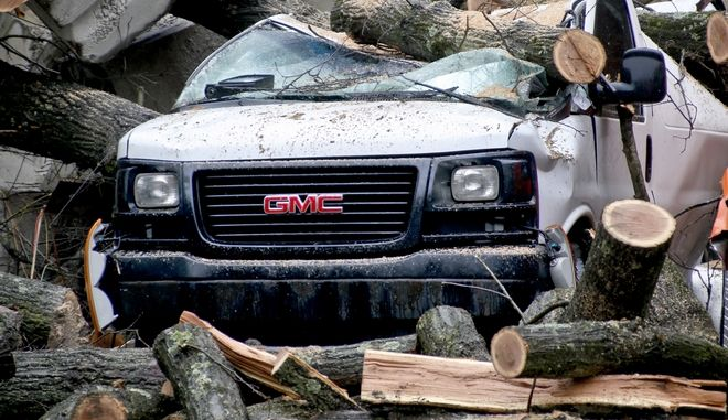 Debris surrounds a truck as workers had cut a tree apart  to free the truck,  Saturday, Feb. 24, 2018 in Millvale, Pa. A landslide on Friday caused trees and concrete stored on top of the hill to tumble onto a business below in the Pittsburgh suburb. Area roads are closed and authorities warn more closing and flooding may be coming with the weekend's continuing rains. (AP Photo/Keith Srakocic)