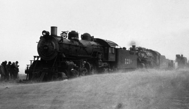 Trainmen in Western Kansas are hoping for relief from a dust storm which made operation of trains difficult. This picture shows a second engine trying to extricate one stalled in a dust drift, April 4, 1935, Dodge City, Ks. (AP Photo)