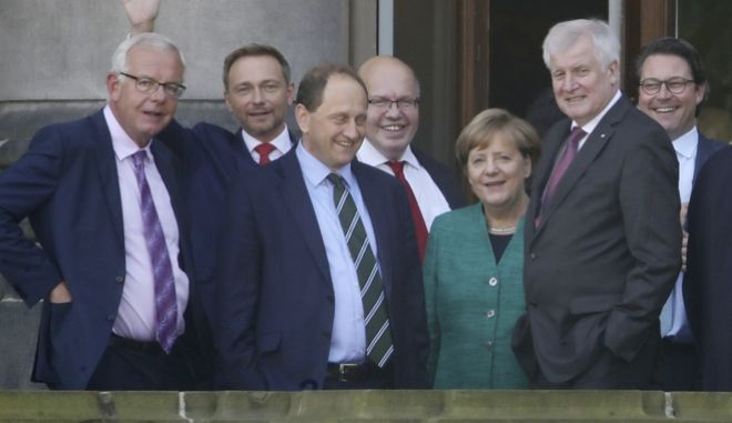 From left: Thomas Kreuzer, faction leader of the Christian Social Union party, CSU, in the Bavarian parliament, Free Democratic party, FDP, chairman Christian Lindner, FDP member Alexander Graf Lambsdorff, Peter Altmaier chief of staff at the chancellery, Bavarian governor and CSU head,  Horst Seehofer,  Secretary General of the CSU, Andreas Scheuer stand on the balcony of a parliament building in Berlin, Germany, Wednesday, Oct. 18, 2017. German Chancellor Angela Merkel is meeting members of three smaller political parties to sound out their red lines ahead of formal talks on forging a coalition government. Merkel's Union bloc is holding separate talks Wednesday with the free-market FDP and the environmentalist Greens. (Michael Kappeler/dpa via AP)