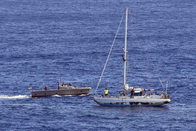 In this Wednesday, Oct. 25, 2017 photo, sailors from the USS Ashland approach a sailboat with two Honolulu women and their dogs aboard as they are rescued after being lost at sea for several months while trying to sail from Hawaii to Tahiti. The U.S. Navy rescued the women on Wednesday after a Taiwanese fishing vessel spotted them about 900 miles southeast of Japan on Tuesday and alerted the U.S. Coast Guard. The women, identified by the Navy as Jennifer Appel and Tasha Fuiaba, lost their engine in bad weather in late May, but believed they could still reach Tahiti. (Mass Communication Specialist 3rd Class Jonathan Clay/U.S. Navy via AP)