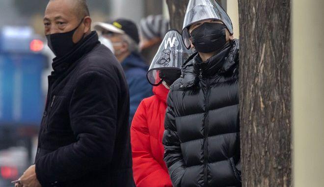 Άνδρας φοράει πλαστική μάσκα προσώπου καθώς περιμένει ένα λεωφορείο σε στάση λεωφορείου στο Πεκίνο