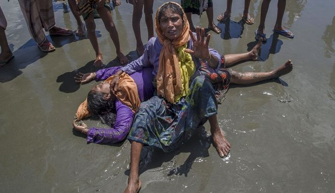 A Rohingya Muslim woman, who crossed over from Myanmar into Bangladesh, shouts for help as a relative lies unconscious after the boat they were traveling in capsized minutes before reaching shore at Shah Porir Dwip, Bangladesh, Thursday, Sept. 14, 2017. Nearly three weeks into a mass exodus of Rohingya fleeing violence in Myanmar, thousands were still flooding across the border Thursday in search of help and safety in teeming refugee settlements in Bangladesh. (AP Photo/Dar Yasin)