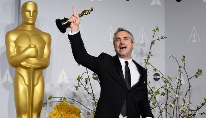 """O Alfonso Cuaron ποζάρει με τα 2 του Όσκαρ για το """"Gravity"""" στην τελετή του 2014.  (Photo by Jordan Strauss/Invision/AP)"""