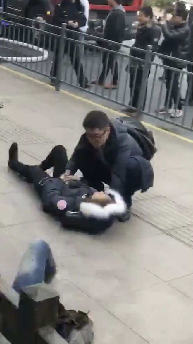 In this image taken from cellphone video provided to the Associated Press, a man tends to an injured person after a minivan carrying gas tanks plowed into pedestrians along a street in Shanghai, Friday, Feb. 2, 2018. A minivan plowed into pedestrians on a sidewalk in downtown Shanghai on Friday, sending more than a dozen people to hospitals. (AP Photo)