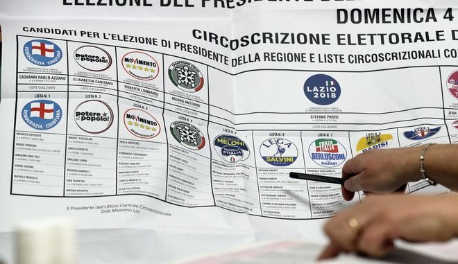 A woman working at a polling station points with her pencil a party symbols list during the Italian general elections in Fiuggi, Italy, Sunday, March 4, 2018. (AP Photo/Gregorio Borgia)