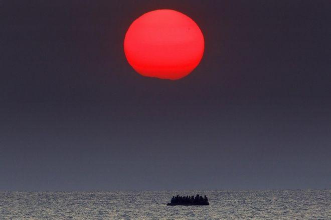 Ο κατακόκκινος ήλιος πάνω από το Αιγαίο, καθώς μια υπερπλήρης βάρκα με πρόσφυγες διασχίζει τη θάλασσα
