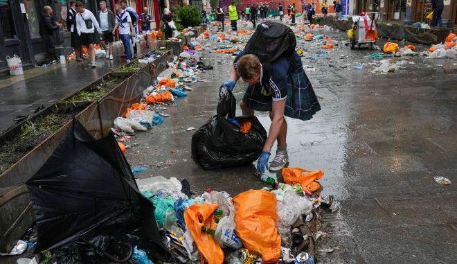 Ένας οπαδός της Σκωτίας βοηθάει στον καθαρισμό πλατείας στο Λονδίνο.