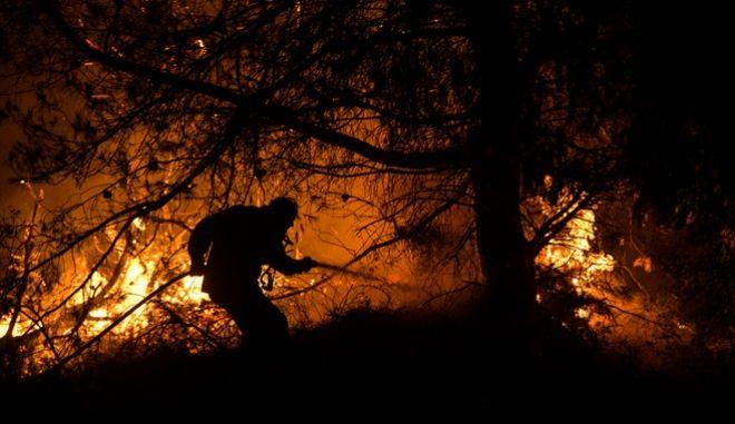 Πυροσβέστες προσπαθούν αργά το βράδυ να περιορίσουν την μεγάλη πυρκαγιά που κατακαίει από τις 3 τα χαράματα της Τρίτης 13 Αυγούστου 2019, την περιοχή Μεσσαπίων-Δίρφυος