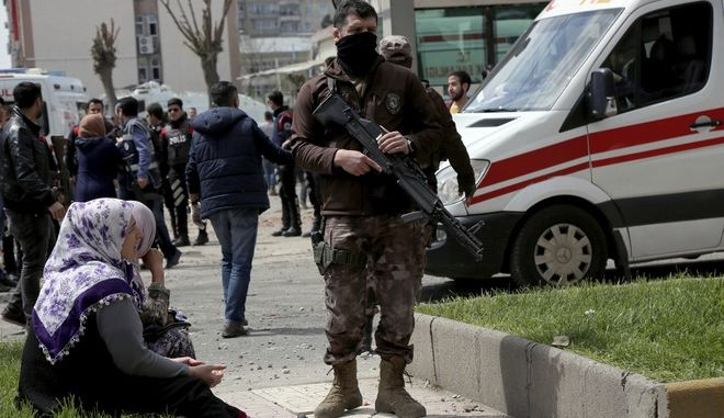 A secury officer patrols near the site after an explosion in Diyarbakir, Turkey, Tuesday, April 11, 2017. An explosion inside a workshop where a police armored vehicle was being repaired killed one man and injured a number of other people, Turkish police said Tuesday. The blast in the mainly Kurdish city of Diyarbakir caused part of the workshop  an annex to the city's main police headquarters  to collapse.(AP Photo)
