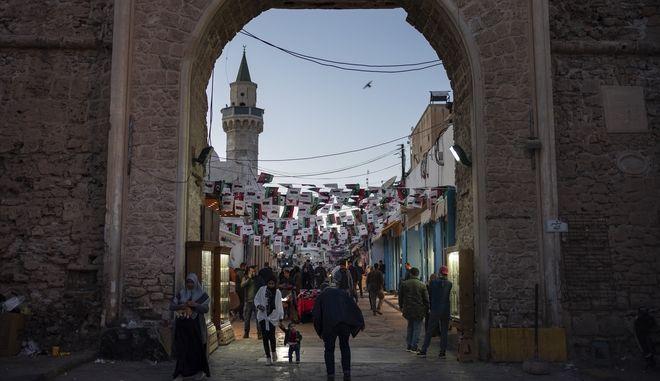 In this Feb. 25, 2020 photo, people walk near one of the entrances of the Old City in Tripoli, Libya. (AP Photo/Felipe Dana)