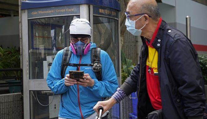Άνθρωποι φορούν μάσκες προσώπου σε δρόμο στο Χονγκ Κονγκ Τρίτη, 25 Φεβρουαρίου 2020