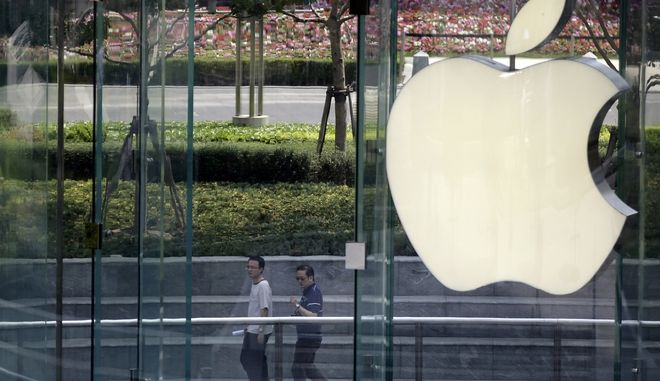 Two men walk near the logo of Apple at an Apple retail shop under construction in Shanghai, China, Tuesday, Sept. 10, 2013. Apple's much-anticipated update to its line-up of iPhones may leave the impression that the technology pioneer's focus has shifted to making more affordable products than engineering innovative breakthroughs. In keeping with its tight-lipped ways, Apple Inc. hasn't disclosed what's on the agenda for the coming-out party scheduled to begin at 10 a.m. PDT (1700 GMT) Tuesday at its Cupertino, California, headquarters. (AP Photo/Eugene Hoshiko)
