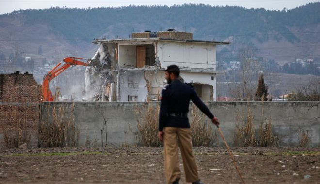 A policeman looks on as the building where al Qaeda leader Osama bin Laden was killed is demolished in Abbottabad February 26, 2012. Pakistani forces began demolishing the house where al Qaeda leader Osama bin Laden was killed by U.S. special forces last May, in an unexplained move carried out in the dark of night.  REUTERS/Faisal Mahmood   (PAKISTA - Tags: POLITICS CRIME LAW)