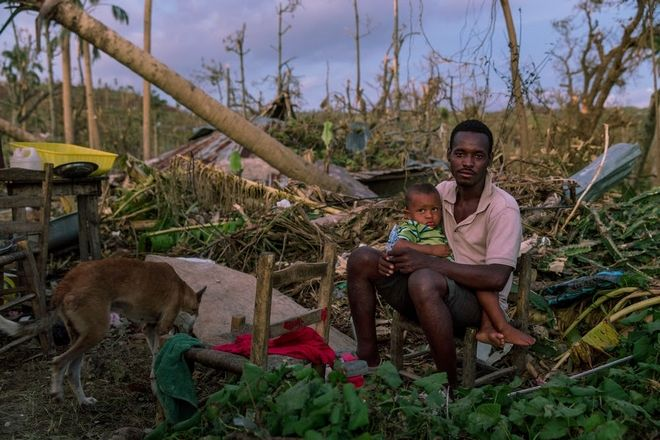 A man sits with his son in a devastated area near Port Salut, in southwestern Haiti. Hurricane Matthew through the Caribbean on October 4 and devastated large parts of the island.