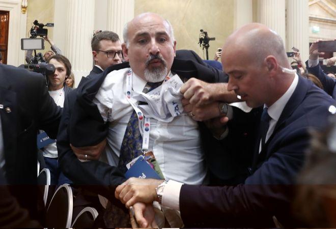 Οι άνδρες της ασφάλειας βγάζουν εκτός αίθουσας άνδρα που επιχείρησε να διαμαρτυρηθεί