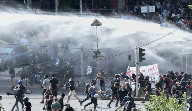 """Η στιγμή που η """"αύρα"""" ρίχνει νερό στους διαδηλωτές."""