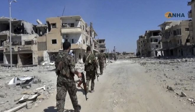 This frame grab from video released Thursday, Aug 3, 2017 and provided by Hawar News Agency, a Syrian Kurdish activist-run media group, shows U.S.-backed Syrian Democratic Forces (SDF) fighters patrolling on a street in the northern city of Raqqa, Syria. U.S.-backed Syrian fighters clashed Thursday with members of the Islamic State group in Raqqa, the de facto capital of the extremists, opposition activists said. (Hawar News Agency via AP)