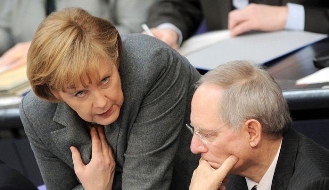 Bundeskanzlerin Angela Merkel (CDU) und Bundesfinanzminister Wolfgang Schäuble (CDU) unterhalten sich am Freitag (19.03.2010) im Plenarsaal des Bundestages in Berlin. Gegen Mittag ist die Schlussabstimmung über den Gesamtetat vorgesehen. Der Etat der schwarz-gelben Koalition sieht für dieses Jahr neue Schulden von 80,2 Milliarden Euro vor. Foto: Rainer Jensen dpa/lbn +++(c) dpa - Bildfunk+++