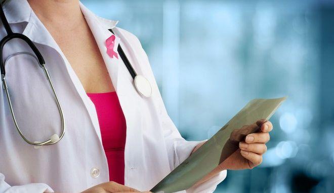 Γιατρός εξετάζει μαστογραφία φορώντας το σύμβολο κατά του καρκίνου του μαστού.