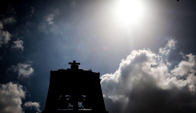 Σύννεφα που κυκλώνουν τον ήλιο με φόντο το καμπαναριό μιας εκκλησίας στο κέντρο της Αθήνας