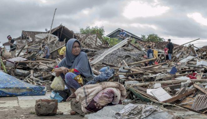 Μια γυναίκα προσπαθεί να καταλάβει τι έχει συμβεί μετά το φονικό τσουνάμι στην Ινδονησία