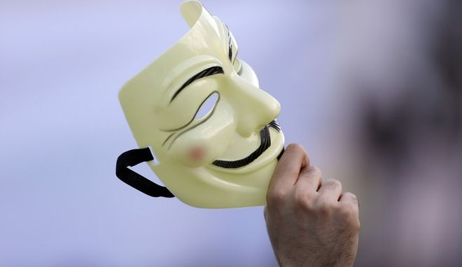 A supporter holds a Guy Fawkes mask during a campaign rally of the Five Stars Movement, in view of the May 25 EU Parliament elections in Rome, Friday, May 23, 2014. (AP Photo/Gregorio Borgia)