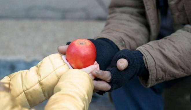 Ένα παιδί προσφέρει ένα μήλο σε έναν άστεγο