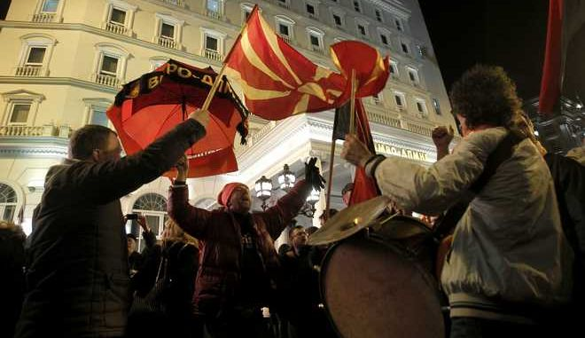 Supporters of the ruling conservative VMRO-DPMNE party celebrate the victory in general elections, in front of the party headquarters in Skopje, Macedonia, early Tuesday, Dec. 13, 2016. Macedonia's dominant conservative coalition has won a narrow victory over the main opposition Social Democrats in early national elections, although without enough seats in parliament to govern alone, final results showed late Monday. (AP Photo/Boris Grdanoski)