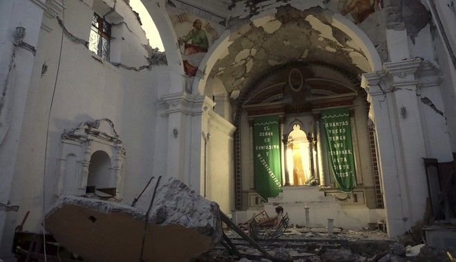CORRECTS AGE OF BABY TO TWO MONTHS, NOT TWO YEARS - The sky is exposed from inside Santiago Apostol church which collapsed during the 7.1 earthquake in the town of Atzala in Puebla state, Mexico, Wednesday, Sept. 20, 2017. According to family related to 11 relatives who died inside the church during Tuesday's quake, the roof collapsed during a Mass held to baptize a two-month-old girl, and the only people who survived were the baby's father, the priest and the priest's assistant. (AP Photo/Pablo Spencer)