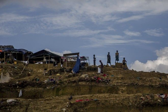 Rohingya Muslim children, who crossed over from Myanmar into Bangladesh, stand over a hillock overlooking refugee camps, in Balukhali, Bangladesh, Tuesday, Sept. 26, 2017. Bangladesh is planning to build separate shelters for 6,000 Rohingya Muslim children who entered the country without parents to escape violence in neighboring Myanmar, a government official said Tuesday. (AP Photo/Dar Yasin)