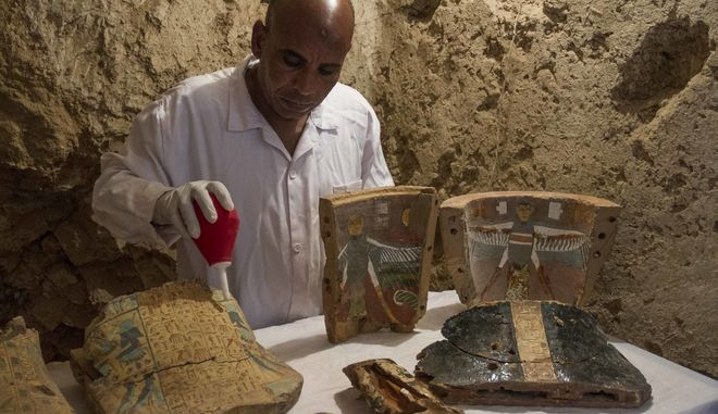 """An Egyptian excavation worker restores funeral furniture found in a newly discovered tombon Luxor's West Bank known as """"KAMPP 161"""" during an announcement for the Egyptian Ministry of antiquities about new discoveries in Luxor, Egypt, Saturday, Dec. 9, 2017. Egypt's Antiquities Ministry says archaeologists have discovered two ancient tombs in the southern city of Luxor. The ministry said Saturday that one tomb has five entrances leading to a rectangular hall, and contains painted wooden funerary masks, clay vessels and a mummy wrapped in linen. (AP Photo/Hamada Elrasam)"""