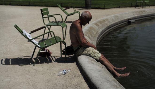 Ηλικιωμένος προσπαθεί να δροσιστεί από τον καύσωνα στο Παρίσι