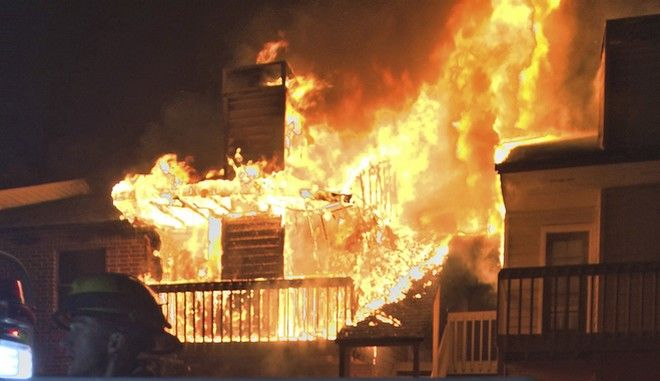 This image provided by the Henrico County Division of Fire shows firefighters responding to a suburban Richmond apartment complex fire early Friday, March, 3, 2017 in Henrico, Va. The fire department said that 20 adults and one child were displaced and it appears 12 apartments will be uninhabitable in the 1:45am blaze that was brought under control in about 90 minutes. (Henrico County Division of Fire via AP)