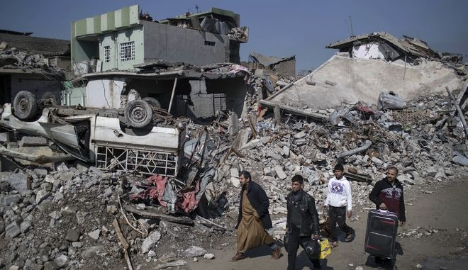 Iraqis walk past debris of houses destroyed during fighting between Iraqi security forces and Islamic State militants on the western side of Mosul, Iraq, Friday, March 24, 2017. Iraqis in the northern city of Mosul are still burying their dead after a U.S. airstrike allegedly killed more than 100 people last week, and rights groups are expressing alarm over a recent spike in civilian deaths. Iraqi officials have defended their conduct in the war against the Islamic State group, and their advice to civilians to shelter in place as U.S.-backed forces seek to drive the extremists from their last urban stronghold in the country.