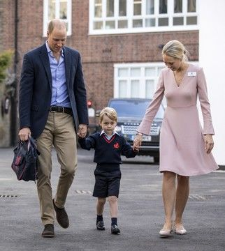 Britain's Prince William, left, accompanies Prince George and Helen Haslem - the head of the lower school on arrival for his first day of school at Thomas's school in Battersea, London, Thursday, Sept. 7, 2017.  Prince William's pregnant wife Kate was too ill with morning sickness Thursday to take young Prince George to his first day of school.  (Richard Pohle/Pool Photo via AP)