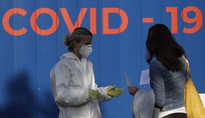 Μια γυναίκα μιλά με εργαζόμενη στον τομέα της υγειονομικής περίθαλψης πριν κάνει το τεστ για την COVID-19 σε ένα σταθμό δειγματοληψίας στην Πράγα της Τσεχίας, 21 Σεπτεμβρίου 2020.