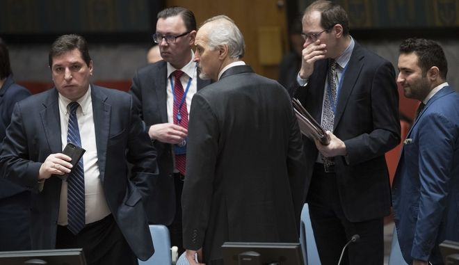 Syrian Ambassador to the United Nations Bashar al-Ja'afari, center, speaks to members of the Russian delegation before the start of a Security Council meeting on the situation in Syria, Thursday, Feb. 22, 2018 at United Nations headquarters. (AP Photo/Mary Altaffer)