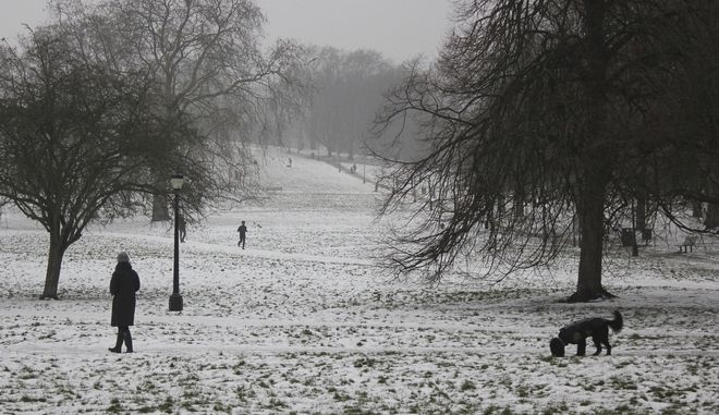 Dog walkers and fitness fanatics seem to be the fearless few in the snow covered Primrose Hill park in London, Saturday, March 3, 2018. Unusually cold weather has gripped much of Europe, with predictions that the deep freeze will continue for the coming days.(AP Photo/Richard Cackett)