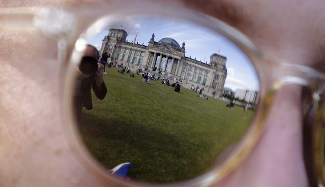 The Reichstag building, which host the German parliament Bundestag is reflected in the sunglasses of a woman ahead of the German general election, in Berlin, Friday, Sept. 22, 2017. German voters will elect their new parliament on Sunday, Sept. 24, 2017, but don't expect a new government to be in place next week. With the seats expected to be spread across up to six caucuses, there's very little chance of anyone winning a majority to govern alone. (AP Photo/Markus Schreiber)