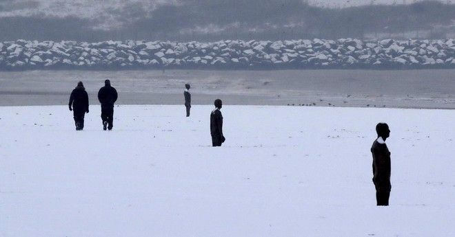People walk  in the snow near to the  Another Place  sculptures by Anthony Gormley, on Crosby Beach near Liverpool, northwest England following heavy overnight snowfall which has caused disruption across Britain. Tuesday Feb.  27, 2018. The freezing snowy weather is expected to continue for a few days (Peter Byrne/PA via AP)