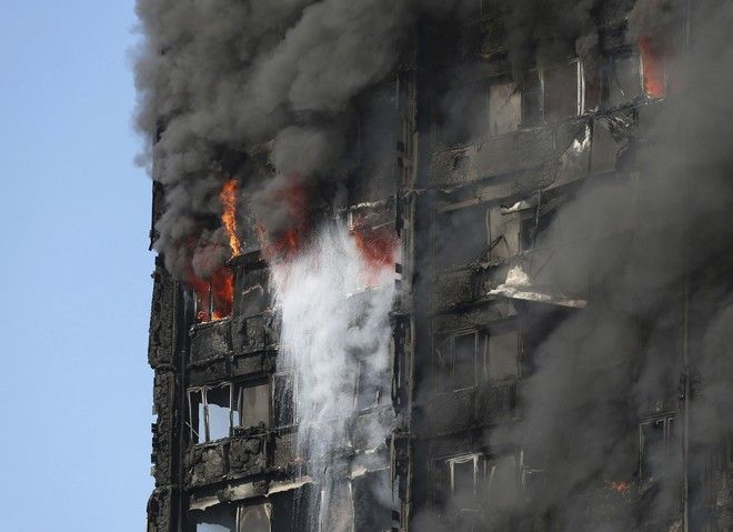 Smoke billows from a high-rise apartment building on fire in west London Wednesday, June 14, 2017. Fire swept through the high-rise apartment building early Wednesday, sending dozens people to area hospitals.  (Jonathan Brady/PA via AP)