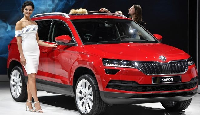 A model poses beside a Skoda Karoq during an event of German carmaker Volkswagen on the eve of the opening of the International Frankfurt Motor Show IAA in Frankfurt, Germany, Monday, Sept. 11, 2017, which runs through Sept. 24, 2017. (AP Photo/Martin Meissner)