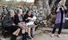 Τρεις ηλικιωμένες ταΐζουν μικρό προσφυγόπουλο στη Λέσβο.