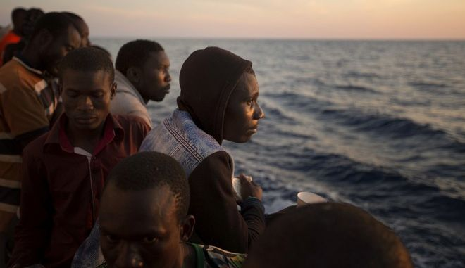 Sub-Saharan migrants stand on the deck of the Golfo Azzurro rescue vessel as they arrive at the port of Pozzallo, south of Sicily, Italy, with hundreds of migrants aboard, rescued by members of Proactive Open Arms NGO, on Saturday, June.17, 2017. A Spanish aid organization rescued more than 600 migrants who were attempting the perilous crossing of the Mediterranean Sea to Europe in packed boats from Libya. (AP Photo/Emilio Morenatti)