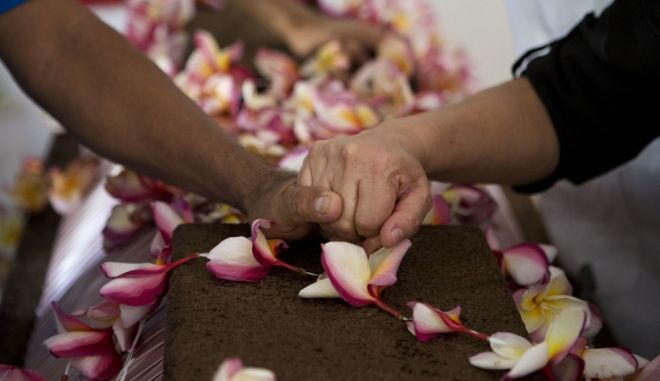 Mourners hold hands over the coffin of 64-year-old Reynalda Matus during a wake in her home, in Juchitan, Oaxaca state, Mexico, Saturday, Sept. 9, 2017. Matus was killed when the pharmacy where she worked nights collapsed during Thursday's massive earthquake. (AP Photo/Rebecca Blackwell)