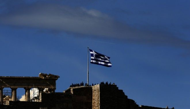 Tourists stand on the Acropolis hill under a huge Greek flag in front of the ancient Parthenon temple, in Athens, on Tuesday, Feb. 12, 2013. Greece battles a sixth year of recession and high unemployment from austerity measures in exchange for ongoing rescue loans from International Monetary Fund and the other 16 European Union countries that use the euro. (AP Photo/Dimitri Messinis)