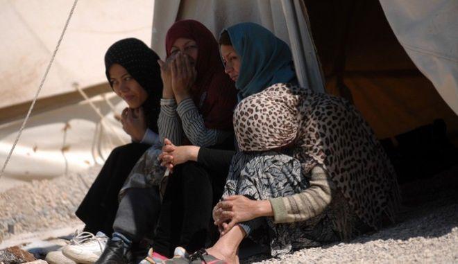 """Γυναίκαες πρόσφυγες κάθονται στον ίσκιο αντίσκηνου, στον καταυλισμό που έχει στηθεί στο στρατόπεδο """"Ευθυμιόπουλου"""" στο Κουτσοχερο Λάρισας την Πέμπτη 31 Μαρτίου 2016. Στον καταυλισμό φιλοξενούνται περισσότεροι από 1500 πρόσφυγες οι περισσότεροι οικογένειες με μικρά παιδιά. Όλοι ζητούν τους επισκεφθεί κάποια κυβερνητική ή κοινωνική οργάνωση που θα μπορεί να τους δώσει απαντήσεις για το θέμα της επανένωσής τους με συγγενείς τους στη Βόρεια και Δυτική Ευρώπη. (EUROKINISSI/ΘΑΝΑΣΗΣ ΚΑΛΛΙΑΡΑΣ)"""