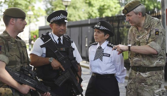 "Metropolitan Police Commissioner Cressida Dick, 2nd right, and Major General Ben Bathhurst, General Officer Commanding London District, right, meet soldiers and police officers on deployment in the Palace of Westminster, London, after Scotland Yard announced armed troops will be deployed to guard ""key locations"" such as Buckingham Palace, Downing Street, the Palace of Westminster and embassies Wednesday May 24, 2017.  Security has been increased in reaction to Monday's explosion in Manchester which killed more than 20 .(Victoria Jones/PA via AP)"